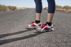 Stock Photo of USA, Arizona, Winslow, Mid adult woman wearing spots shoes standing, low section