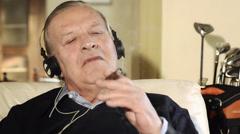 Senior man smoking cigar and listening to music Stock Footage