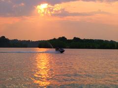 Waverunner crosses lake at sunset 01 Stock Footage