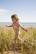 Beaver Island, Girl running in grass on beach, Beaver Island, Michigan, USA Stock Photos