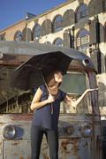 USA, New York City, Brooklyn, woman with umbrella checking for rain - stock photo