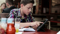 Teenager doing homework with tablet computer in cafe HD Stock Footage