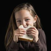 Young girl eating a sandwich Stock Photos