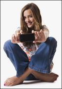 Young girl holding cellular phone Stock Photos