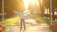 Test passed! Man enjoys himself in sunny park celebrates victory Stock Footage