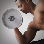Muscular man lifting a dumbbell - stock photo