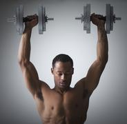 Stock Photo of Muscular man lifting dumbbells