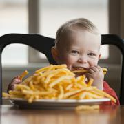 Toddler eating a large plate of French fries Stock Photos