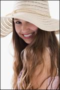 Smiling long haired woman wearing a straw hat - stock photo