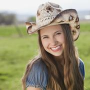 Smiling long haired cowgirl - stock photo