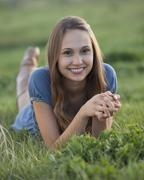 Beautiful long haired woman relaxing on the grass - stock photo