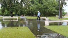 Man cleans storm rain water drain in flooded park Stock Footage