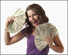 Young woman holding fanned out banknotes - stock photo