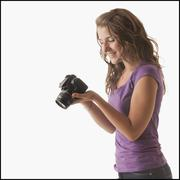 Stock Photo of Young woman holding camera