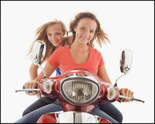 Young girls (16-17) riding scooter - stock photo