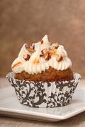 Delicious carrot cake cupcake with cream cheese frosting and nuts Stock Photos