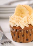 Stock Photo of delicious carrot cake cupcake with cream cheese frosting, sliced bananas and