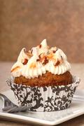 delicious carrot cake cupcake with cream cheese frosting and nuts - stock photo
