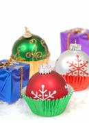 Christmas ornaments in cupcake liners with gifts Stock Photos