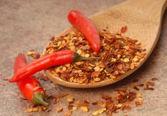 Red chili peppers and red pepper flakes on a spoon Stock Photos