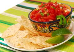 Tortilla chips with salsa and lime Stock Photos