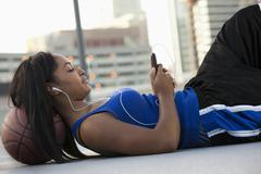 Stock Photo of USA, Utah, Salt Lake City, Young woman lying on basketball and listening to mp3