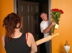 Husband coming home late to angry wife Stock Photos