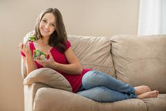 Stock Photo of Portrait of young woman eating salad