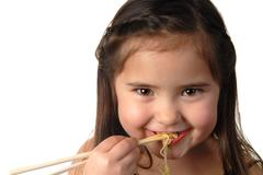 Young girl eating noodle soup Stock Photos