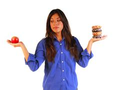 young woman deciding to eat apple or donuts - stock photo