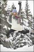 Stock Photo of USA, Utah, Salt Lake City, portrait of young woman in winter clothing leaping