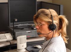 police dispatcher sitting at a dispatch console - stock photo