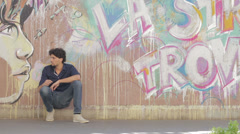 Young man resting after a long walk - beautiful graffiti in background Stock Footage