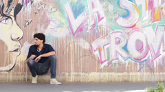 Sad young man - wall with graffiti in background Stock Footage