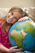 Stock Photo of USA, Utah, Lehi, Cheerful girl (8-9) sitting on sofa with globe on knees