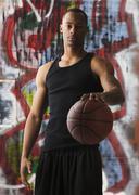 Stock Photo of USA, Utah, Salt Lake City, portrait of basketball player in front of graffiti
