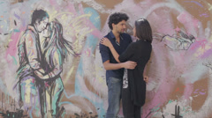 A boy and a girl swear eternal love and kiss, in graffiti on the wall is painted Stock Footage