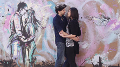 Loving couple kissing in graffiti behind a couple kissing - love - hug Stock Footage