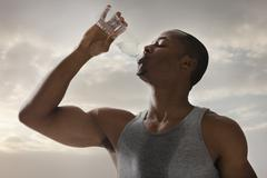 Stock Photo of USA, Utah, Salt Lake City, Athlete young man drinking water form bottle, cloudy