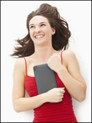 Young woman embracing electronic organizer - stock photo