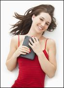 Studio portrait of young woman holding electronic organizer - stock photo