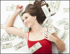 Stock Photo of Young woman lying in money