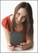 Studio portrait of young woman using electronic organizer - stock photo