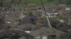 Crane operating in residential neighborhood, lifting materials over homes Stock Footage