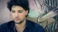 portrait Sad, depressed young man  sitting near a graffiti wall HD Footage