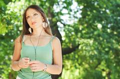 Girl listening to music with earphones in a park, sunny day - stock photo
