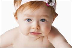 Portrait of baby girl (6-11 months) looking at camera, studio shot - stock photo