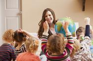 Stock Photo of Geography teacher with children (2-3, 4-5) raising hands
