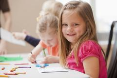 Stock Photo of Girl (4-5)  looking at camera during art lesson in kindergarten