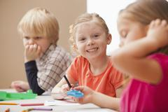 Girl (4-5)  looking at camera during art lesson in kindergarten - stock photo